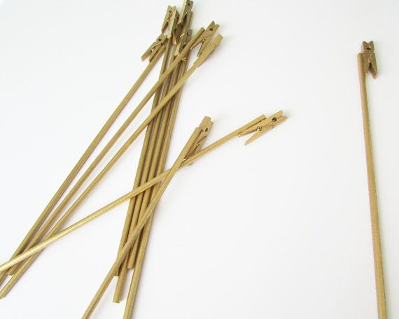 This order takes 3-5 business days to put together. It then takes additional time for shipping. <<<  ..................Details.....................  - Set of 15 gold table number holders - These do not have bases - Stick them in a jar with flowers for a simple centerpiece! - Made from a 1 3/4 inch clothespin and a 12 inch dowel - Total height is 12 1/2 inches (31.75cm) - Each piece may vary slightly since these are hand made - Message me if you need a bigger or smaller holder - See my shop…