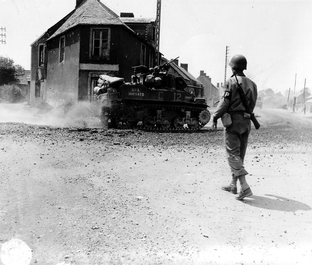 """An American M5A1 light tank called """"Concrete"""", the Charlie Co, Bn Light Tank, an Armored Regiment, 2nd Armored Division of the USD. The Policeman is part of the MP Platoon of the 2nd Armored Div. US. A convoy to the tile, Tronquay hamlet, comes from the GC73 Balleroy via Castillon and takes the road to Saint-Lô N172 via Vaubadon. July 17 we are on the eve of the capture of St. Lo, the division is in reserve in the area of Ballymena on 15 as it carries out security missions."""