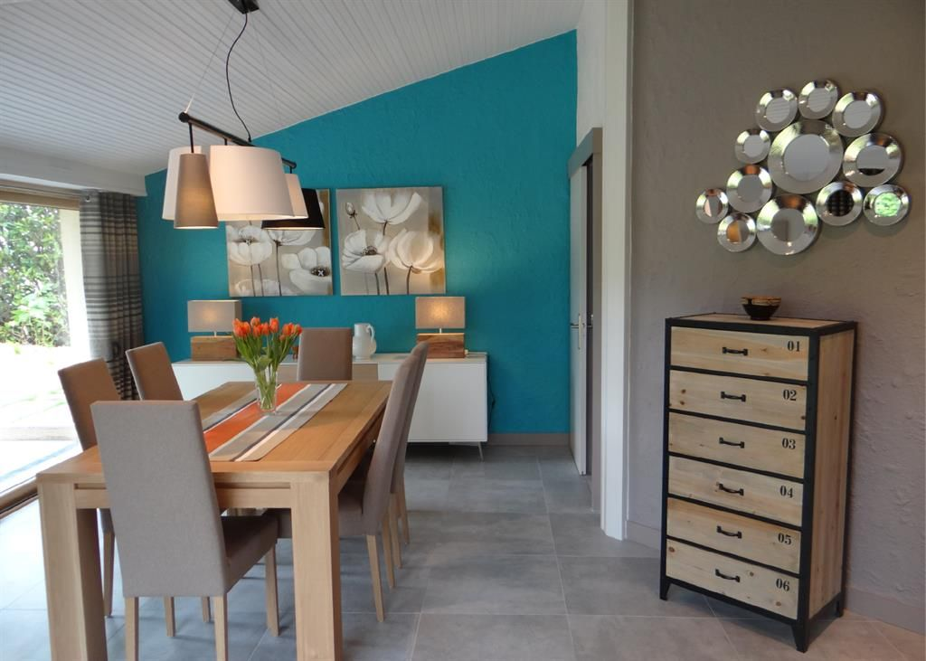 Modern style dining room with a blue wall in contrast with the ...