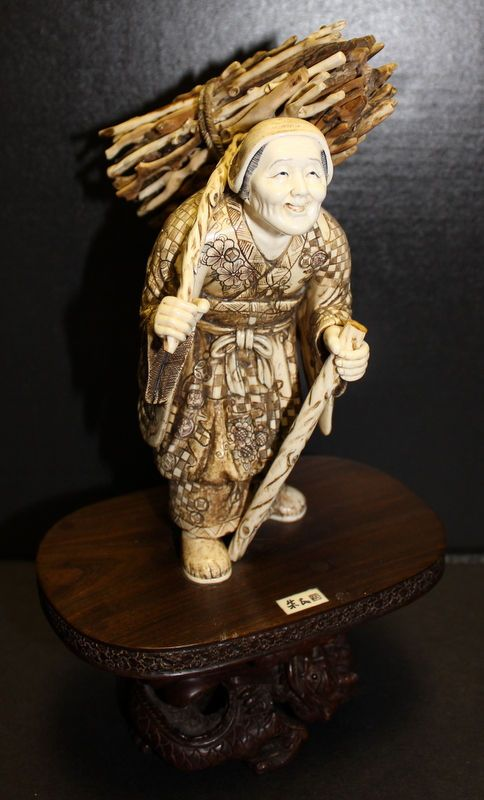 """Late 19th C. Carved Ivory Okimono Old Woman Figurine. Featuring an old woman with walking stick carrying a large satchel of fire wood, decorated with amazing hand scrolled details throughout, atop a hand carved teak wood oval base signed on ivory reserve, measuring 11"""" tall x 4 1/4"""" wide."""