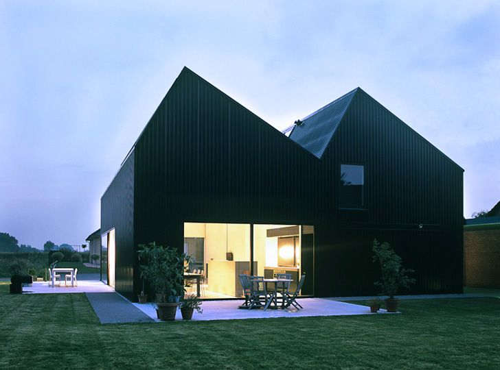 Situated in a typical agricultural village in Flemish area, this single family house has saw-toothed factory roof and black rippled plaster facades, distin