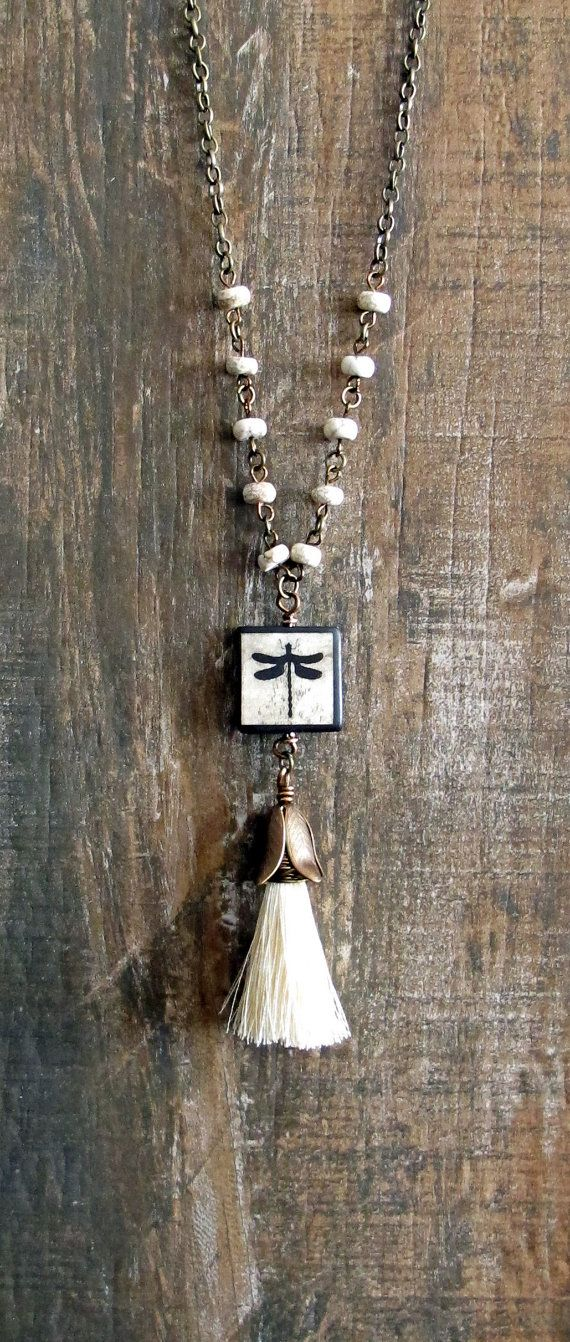 #ThePaintedCabeza ~ This beautiful necklace is made up of a cream colored silk tassel, wire wrapped, and hanging from a dragonfly on a wood tile. The chain is made