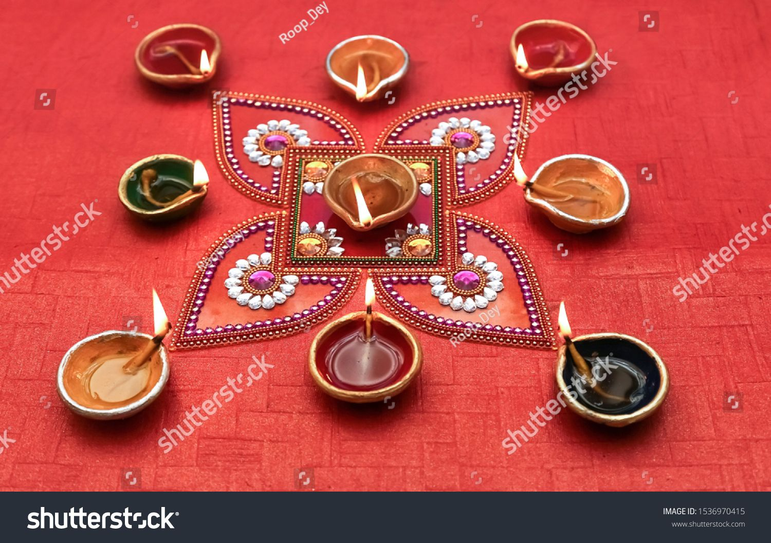 Diwali clay lamps with traditional rangoli design on red