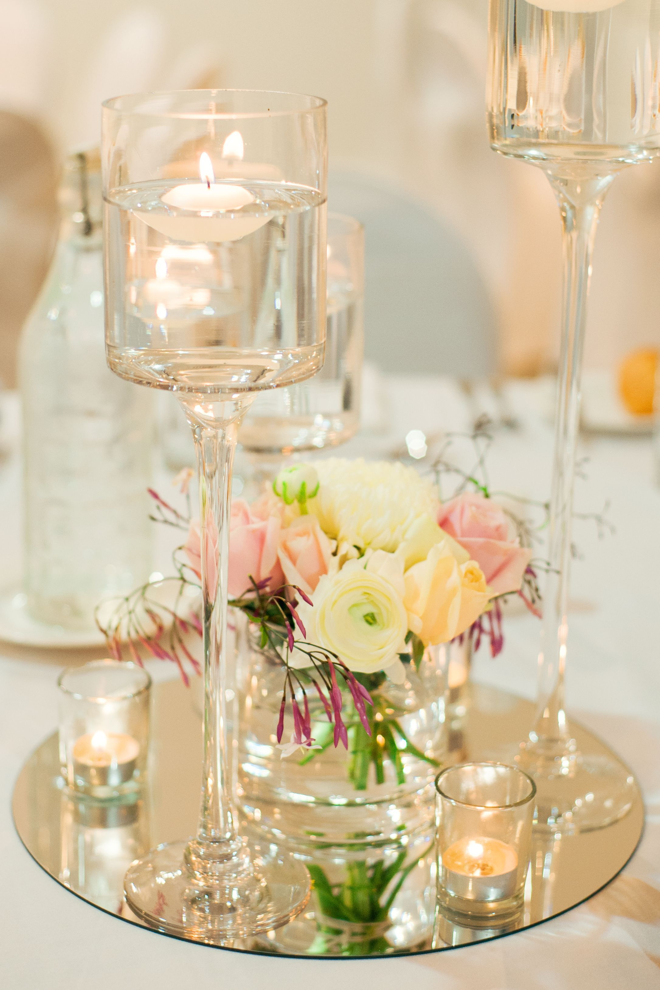 Floating candle centerpiece on a round mirror base with fresh
