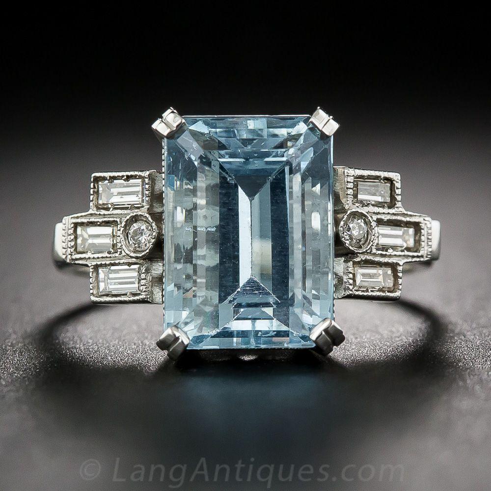 Una refrescante azul de talla esmeralda Aquamarine brilla entre arreglos geométricos de diamantes baguette rectas (más un pequeño diamante redondo) en este chuchería de finales del Art Deco, elaborados en platino y que data de mediados del siglo pasado. El aqua mide 7.16 por 5.16 pulgadas con un peso estimado de 4,75 quilates. Tamaño del anillo 7 1/4.