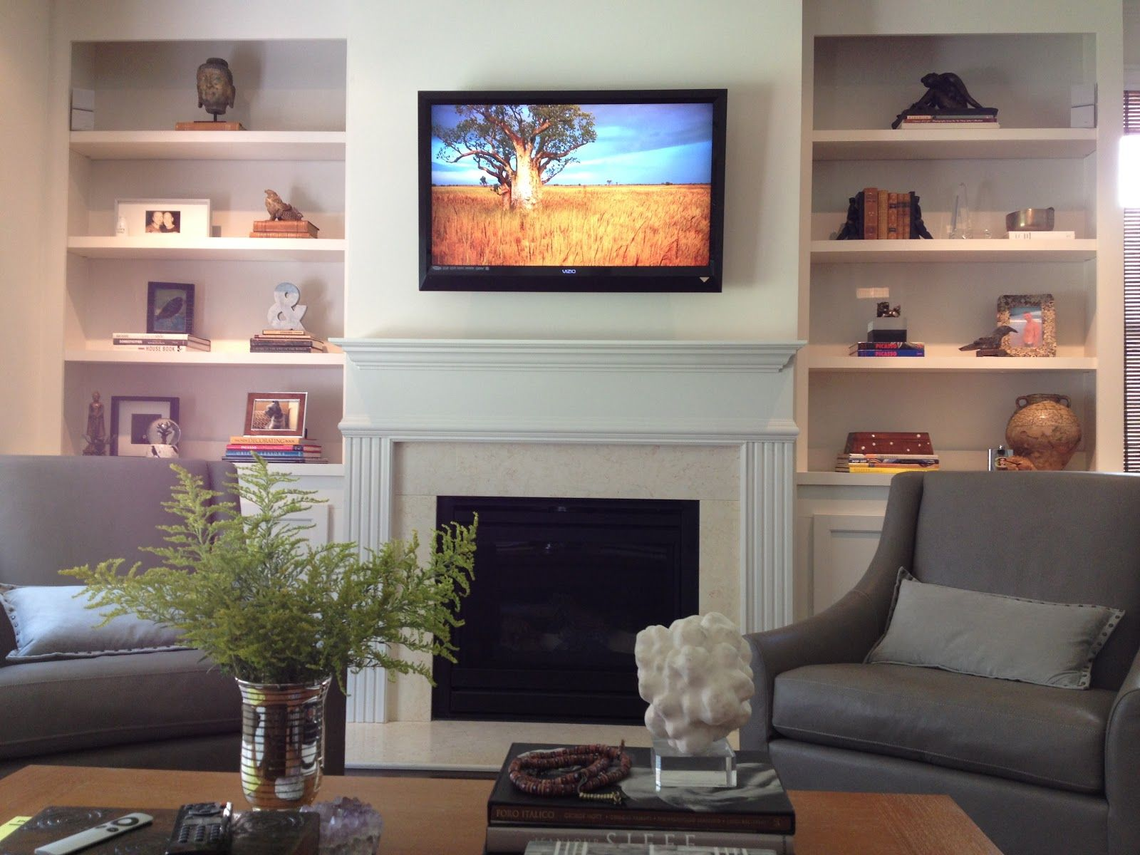 Built in bookshelves and cabinets tv on wall with fireplace below