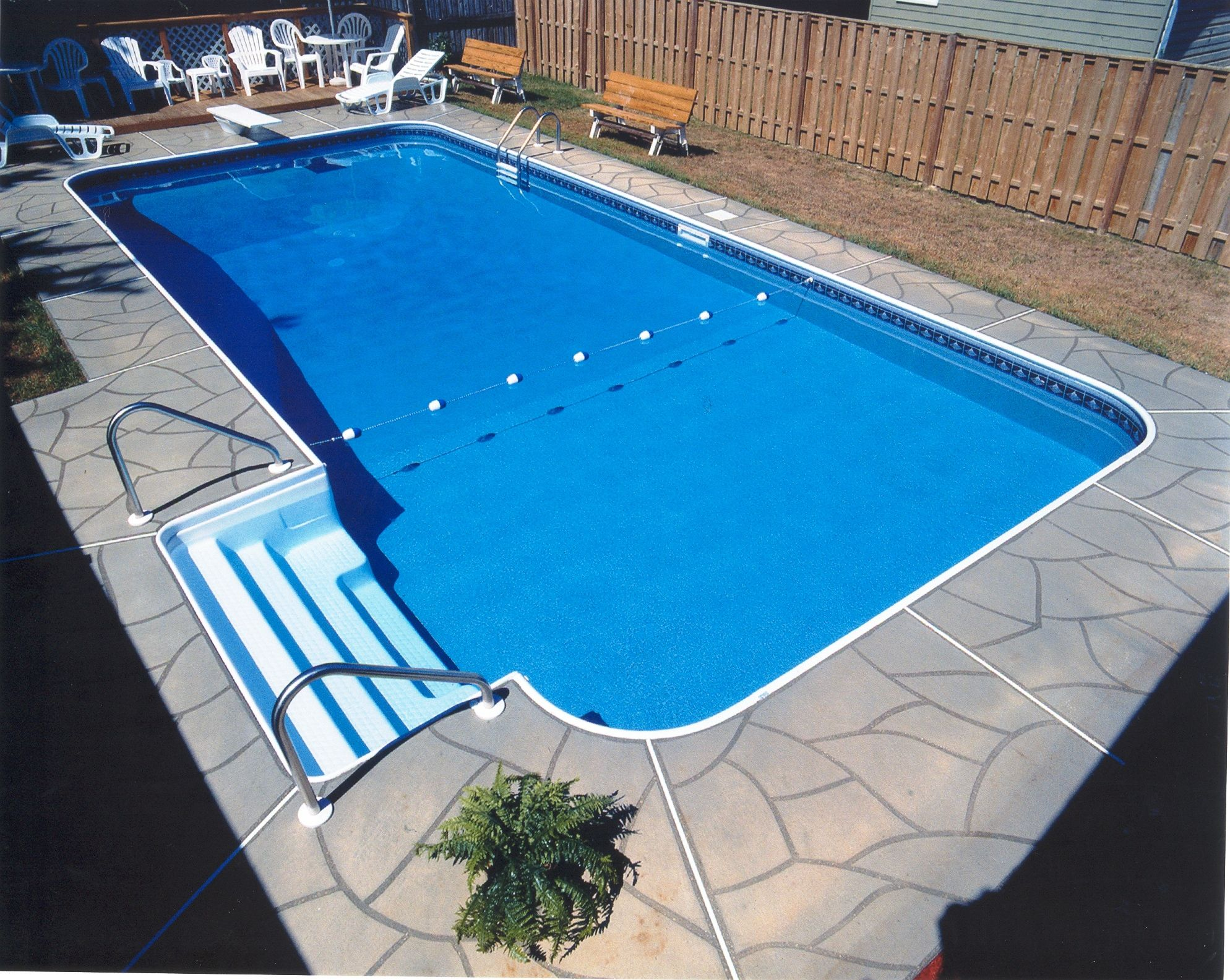 This rectangle pool features a stamped concrete deck and Legacy ...