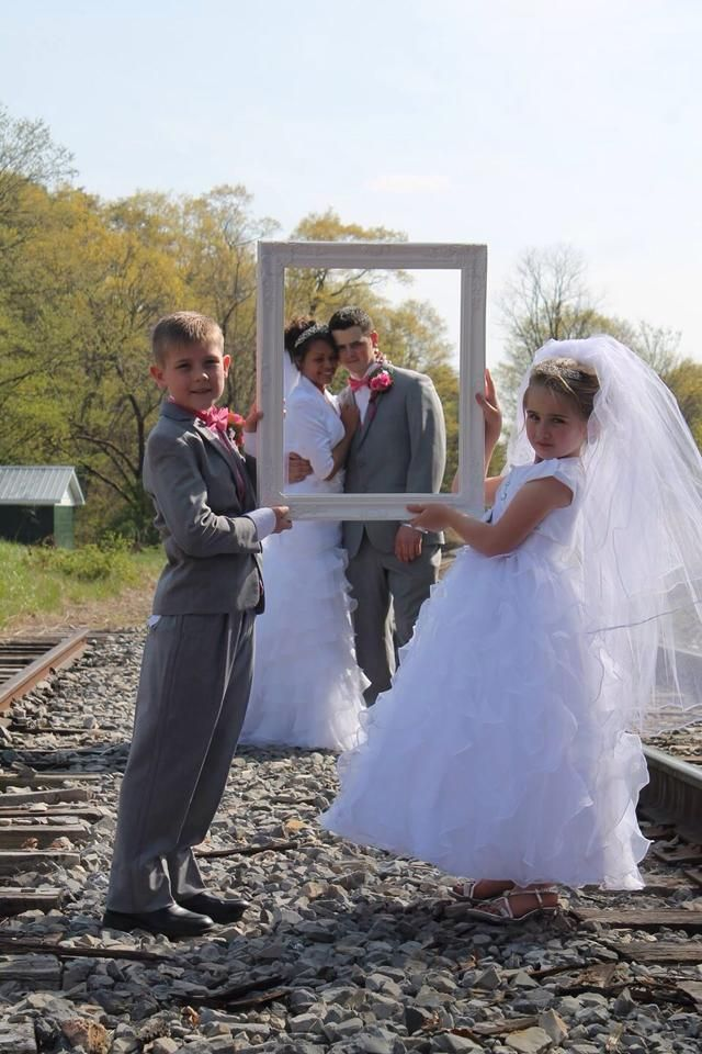 Cute photo idea. Have the flower girl and the ring barrier (if their old enough) hold a picture frame and have the bride and the groom standing behind it.