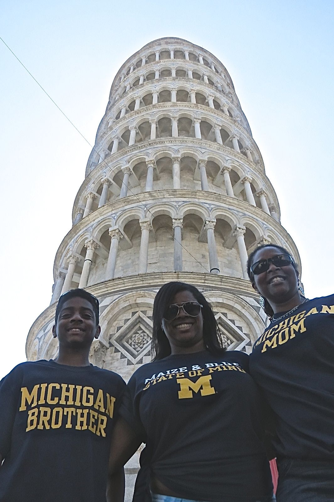 Rozelle Hegeman-Dingle, PHARMD'93 (right) and her son John and daughter Ryan (middle), who is attending U-M beginning this fall, proudly wear their U-M gear while standing in front of the Leaning Tower of Pisa in Italy.