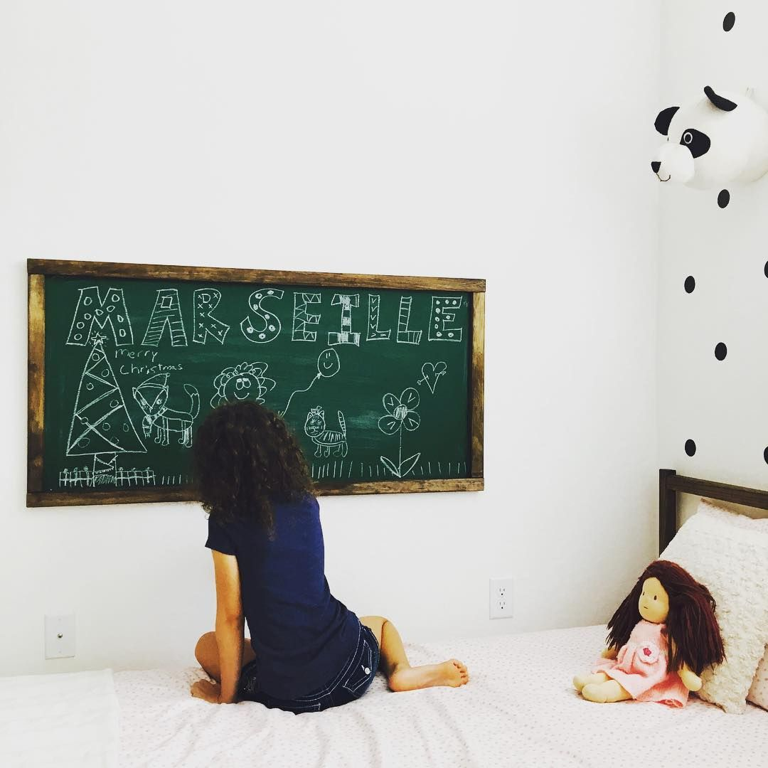 Chalkboard on kids wall, green chalkboard with wood trim. Black decal dots on white kids room wall.