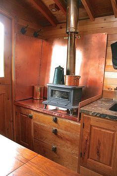 Tiny wood burning stove - I love how it is up off the ground, so it doesn't take up floor space, and it is easier to cook off of. Perfect!!