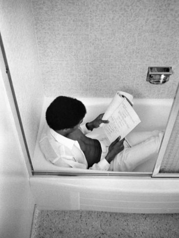 A seeker of quiet places in which to read and write, Richard Pryor reviews scripts in his home bath tub. 1967.    Photo by Bill Gillohm.