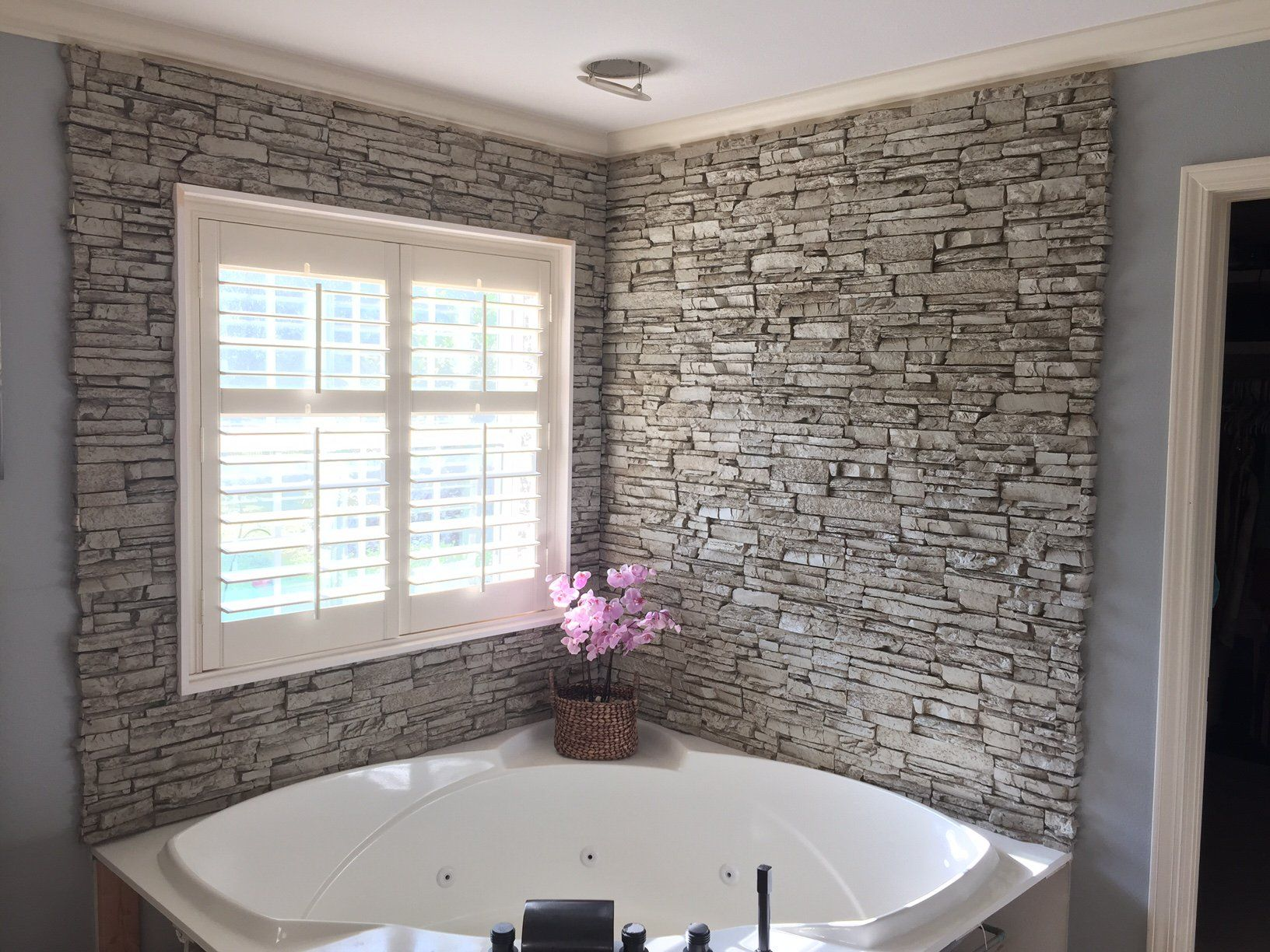 see the bathtub wall surround created with the look of real stacked stone that turned a luxury corner bath into a stunning showpiece