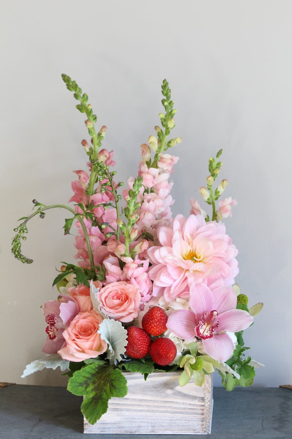 A lush arrangement of pink flowers in a white wash wooden