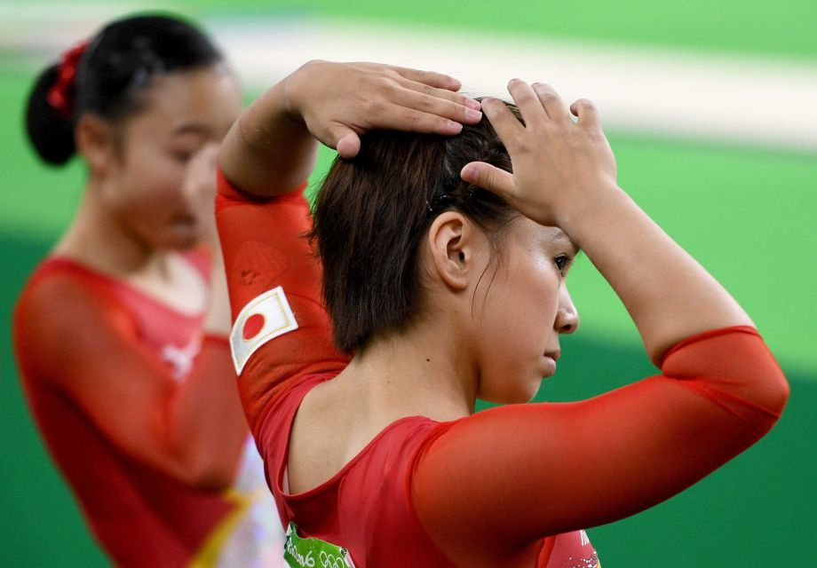 Mai Murakami of Japan is photographed with teammate during the artistic gymnastics women's team final.  Photo by newsday.
