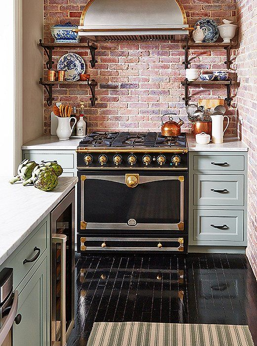 Farmhouse Country Kitchen With A French Oven Exposed Brick Backsplash And Rustic Open Shelving