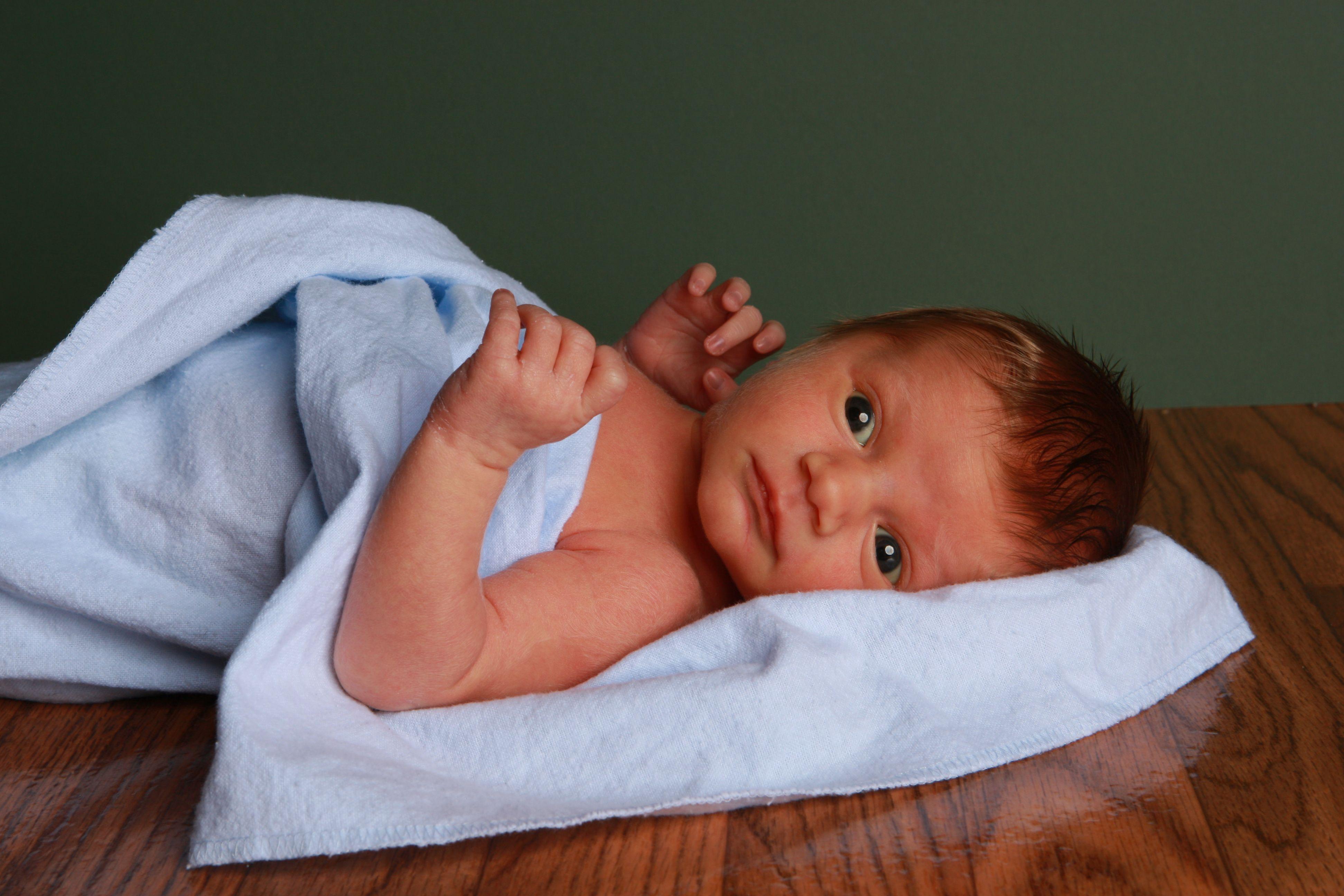 Newborn laying on back blue blanket sanford