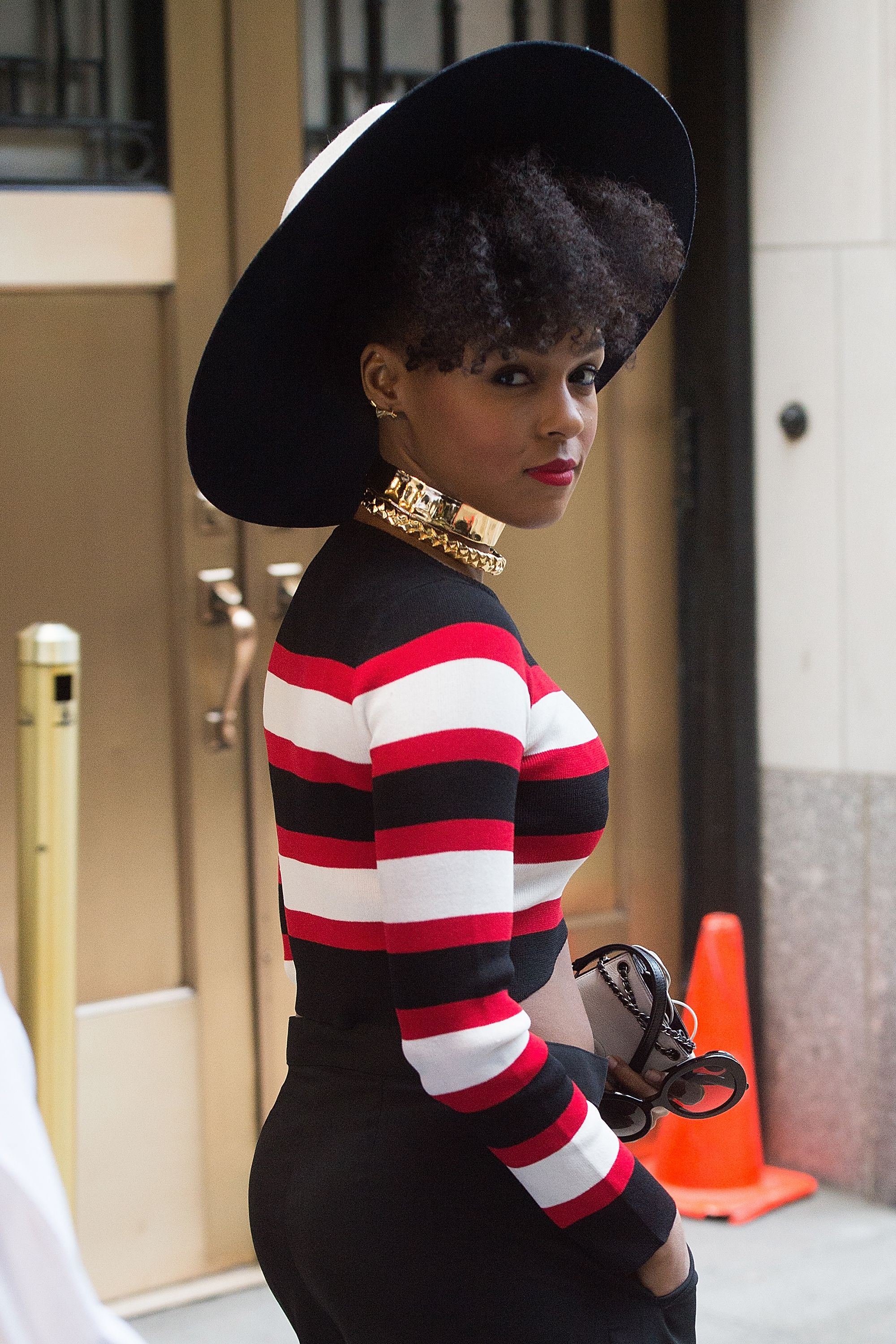 Known for her beauty risks, Monae keeps it playful with curls tumbling out of a wide brim hat, and a bright red lip that makes a statement, too.   - ELLE.com