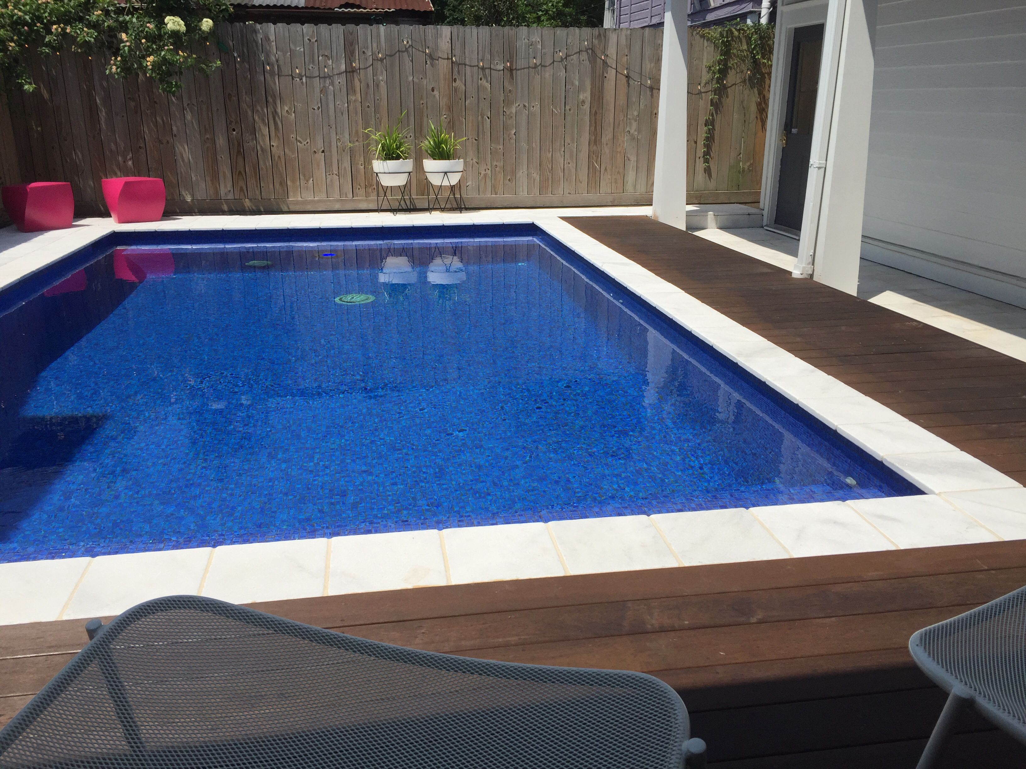 Oiled Ipe deck and snow white travertine against blue tile pool ...