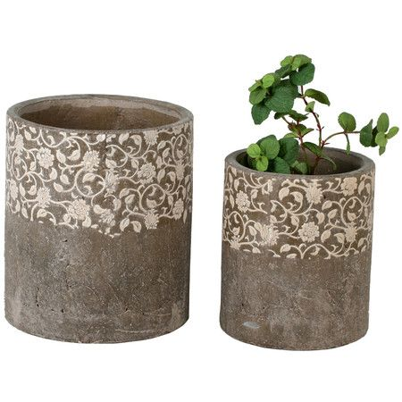 Two-piece ceramic floral pot set with white scrolling detail against a rustic natural finish.   Product: Small and large pot...