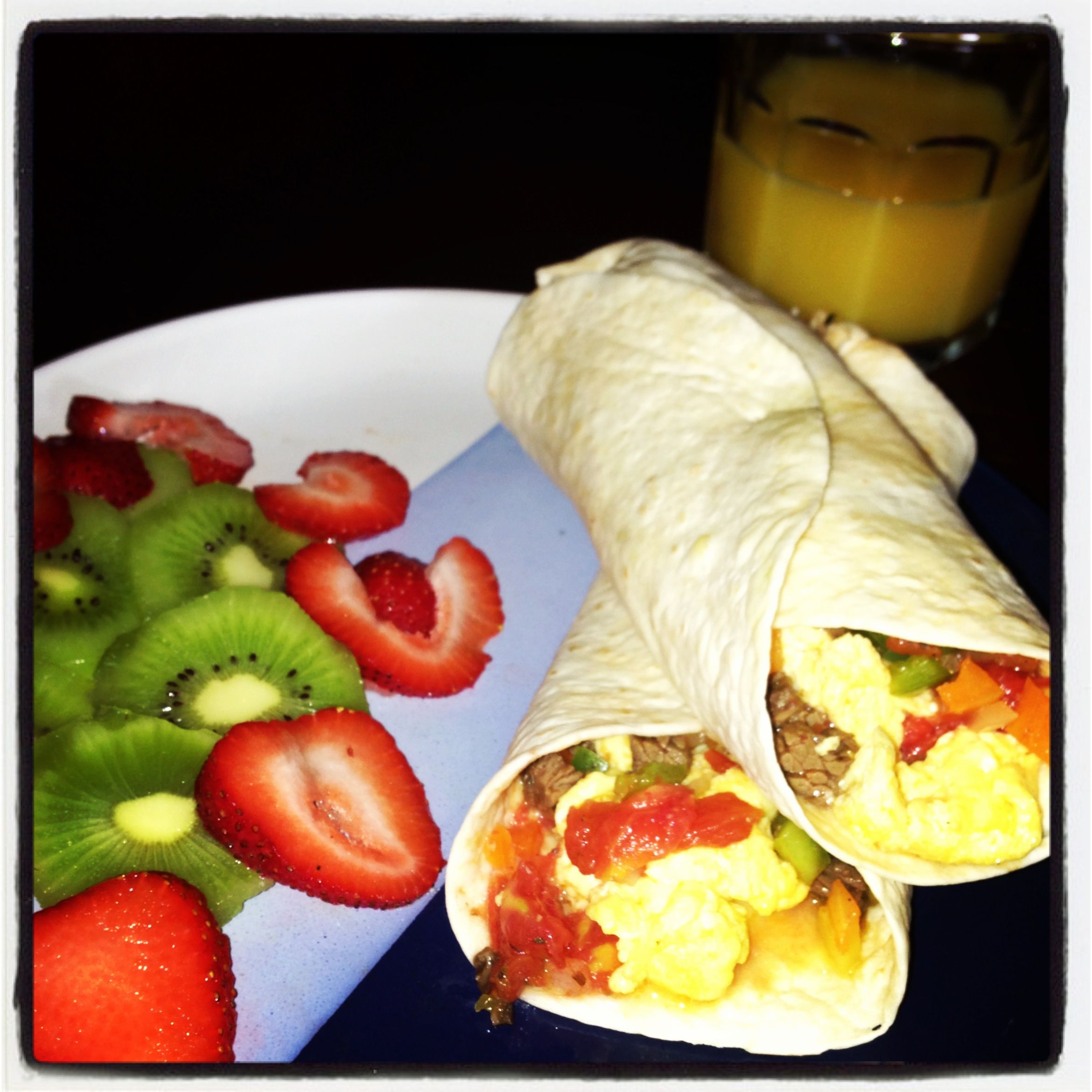 Breakfast burritos Burritos with scrambled eggs mixed with diced bell peppers, onions, tomato and steak! With a side of sliced kiwi and strawberries and oj to drink.