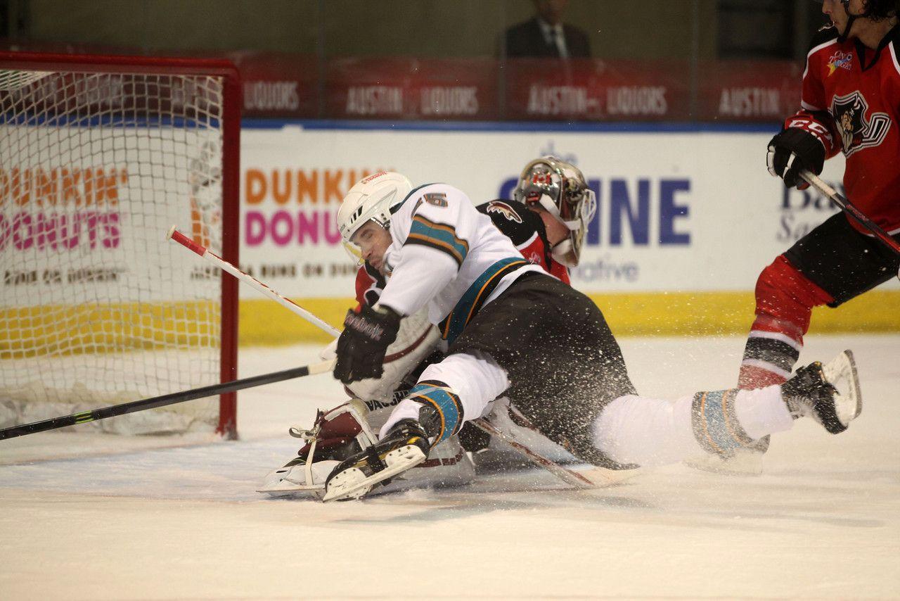 Worcester Sharks forward Marek Viedensky goes crashing into Portland Pirates goaltender Mark Visentin (Dec. 6, 2013).