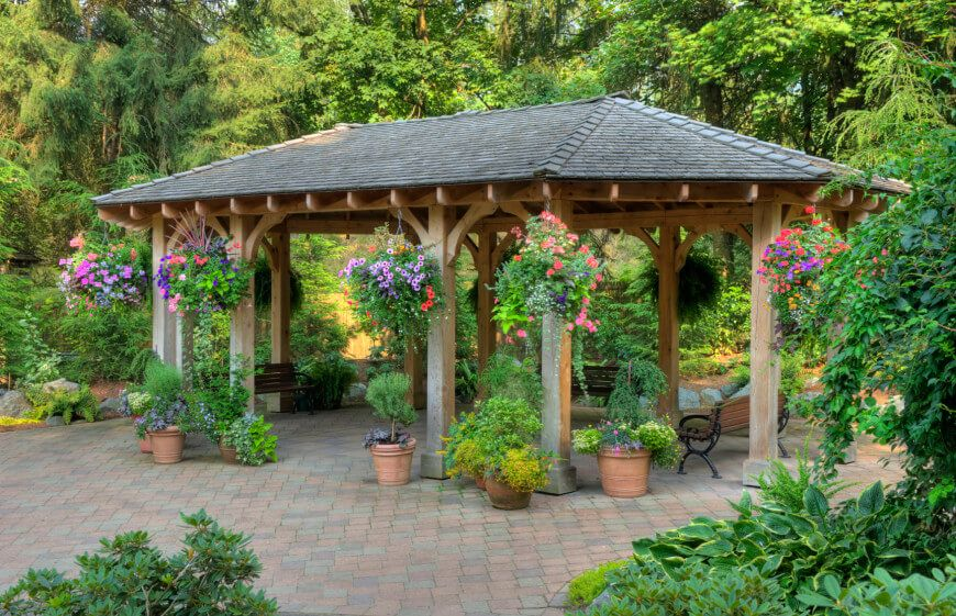 This Patio Gazebo Houses A Few Benches And A Number Of Potted Plants.  Gazebos Work