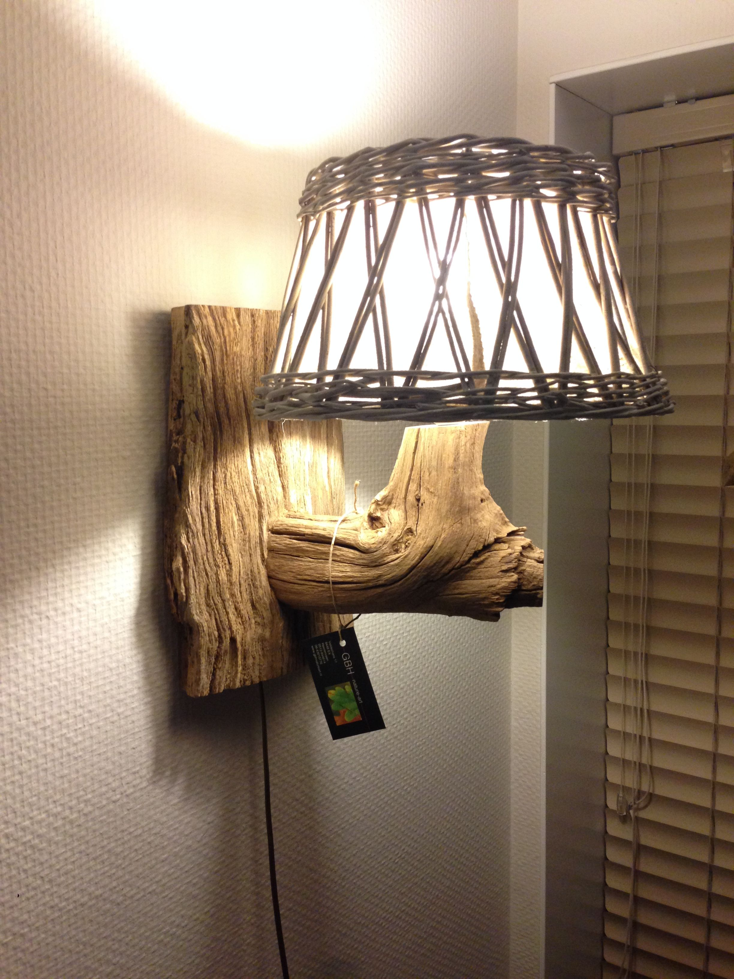 Wall lamp by weathered old oak branch with wicker lampshade