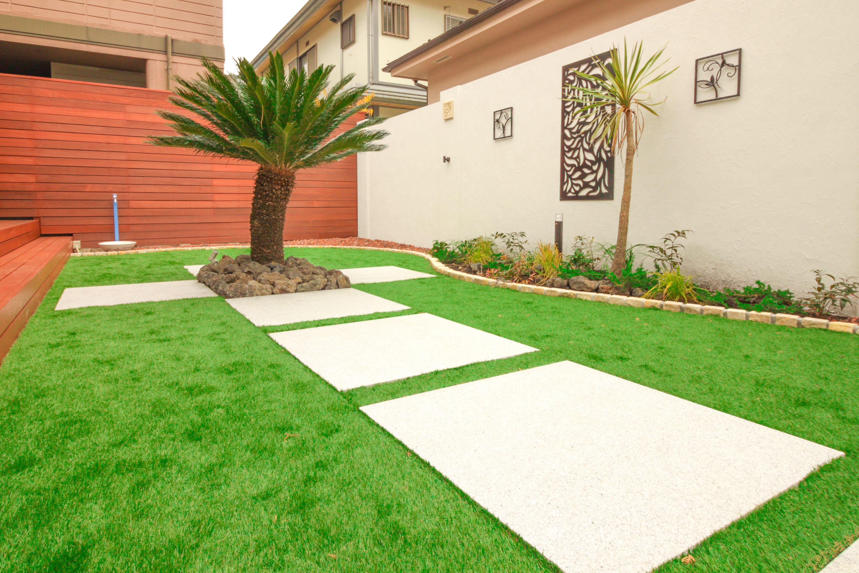 人工芝を張ったお庭に大き目の平板を大胆に敷石 フォーカルポイントとなるソテツをシンボルツリーとして植えたお庭リフォーム 庭 リフォーム 外構 ウッドデッキ ソテツ ハワイアン ハワイ風 シンボルツリー 植栽 風景彫刻 ソテツ 庭