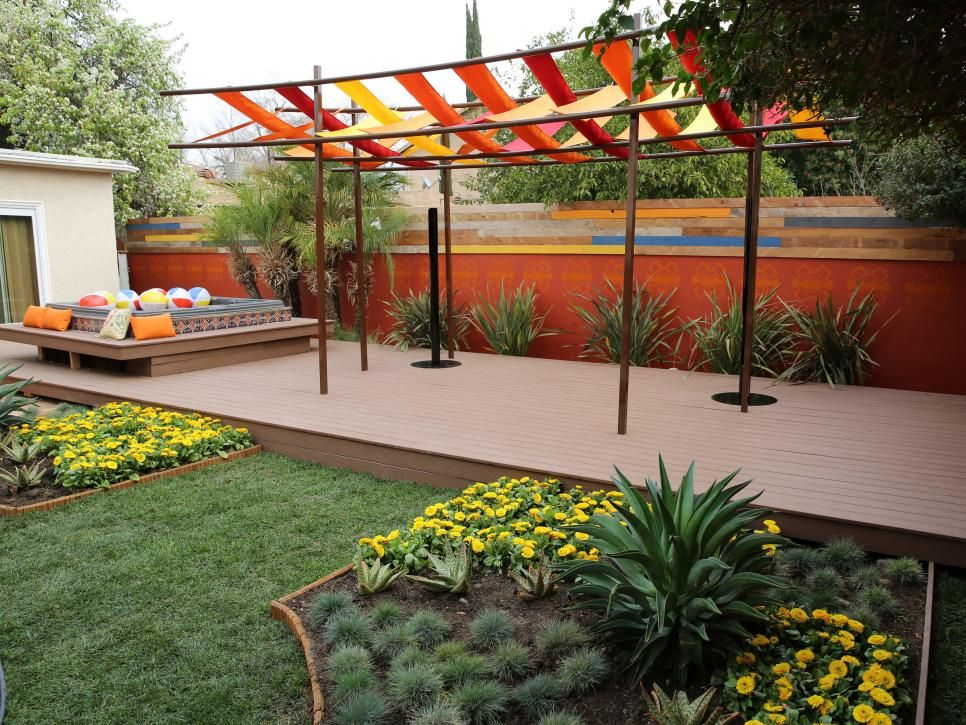 A handpainted Mexican tile hot tub, painted cinderblock wall and unique canvas pergola create a vibrant palette in this fiesta-worthy backyard. See the full makeover + more must-see backyard deck and patio makeovers here >>