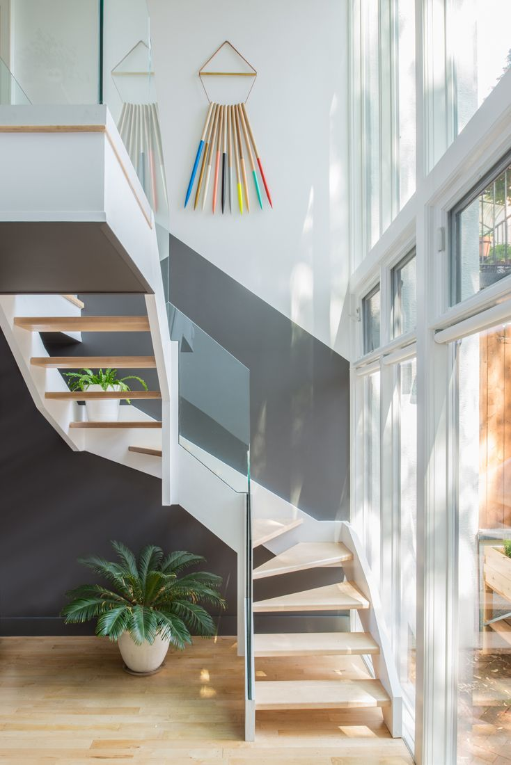 the back staircase abuts a glass facade overlooking the backyard