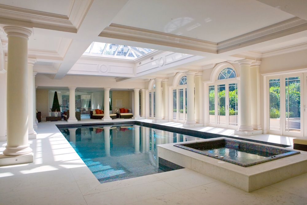 classical architectural columns dramatize these beautiful indoor swimming pools skylights and big windows draw natural light into the interiors - Big House With Indoor Swimming Pool