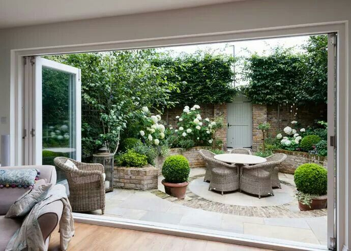 Round patio with wall around it. Bifold doors opening up fully.