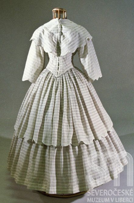 circa 1855 google translate-Women druhorokokové dress handmade from fine cotton fabric with a printed stripe pattern in white and gray-beige color. Under the smaller oval neckline sewn peleríne style large collar with wave-like edge. Tight bodice with fallen shoulders waist extended to the tip, front boned and decorated with ribbons, lace up back. Krinolínová frilled skirt at the waist, upper skirt and wide three-quarter sleeves decorated with wave-like, white selvage edge.