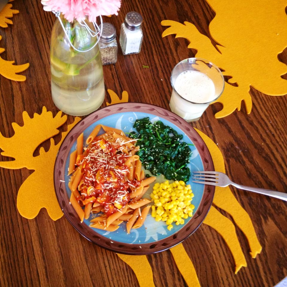 tomato/carrot pasta topped with veggie spaghetti sauce including homegrown squash. steamed sesame/garlic spinach, corn, and soymilk on the side.