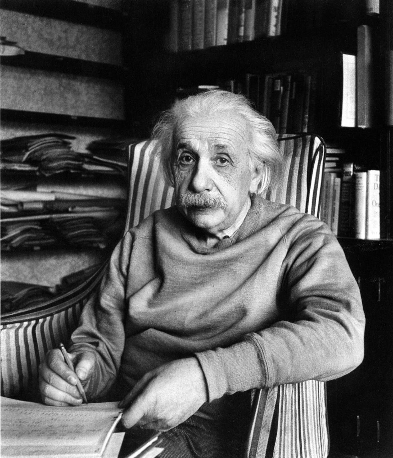 Alfred Eisenstaedt: Albert Einstein in chair writing with pencil,  Princeton, NJ, 1949