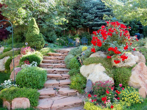 Stairs lead to a flat rock patio enclosed by lush green ...