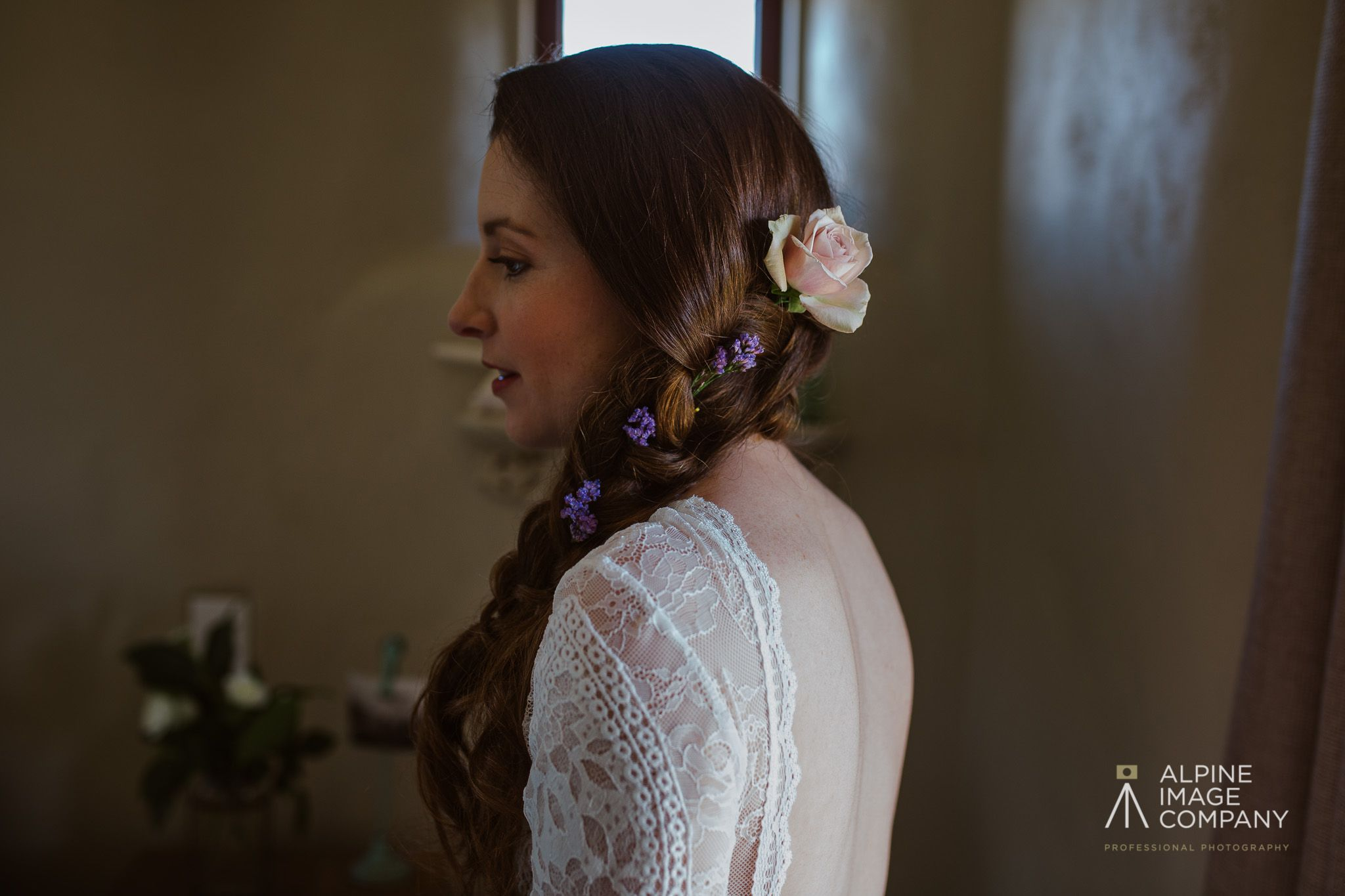 braided hair style with loose curls and fresh flowers. hair by sara