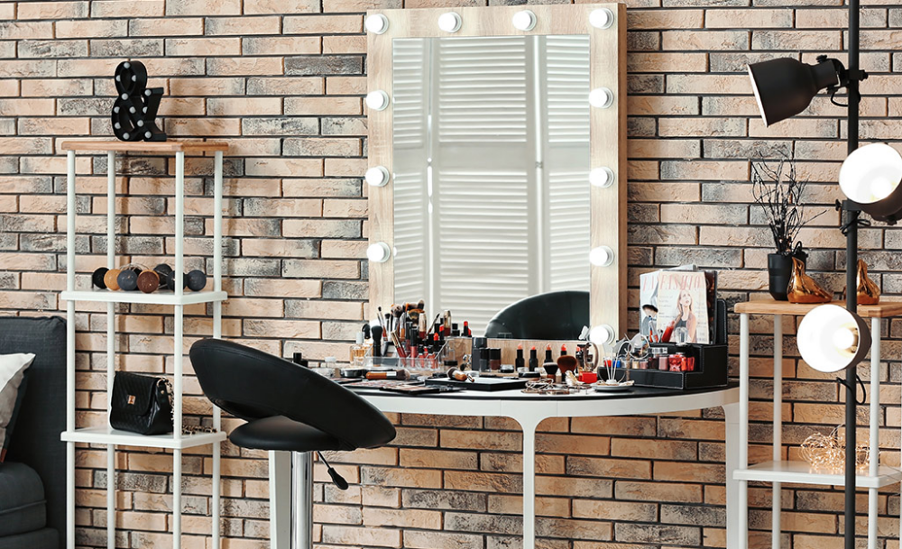 Large lighted makeup mirror resting on metal table