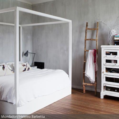 Ein Traum aus Holz: Das minimalistische Himmelbett und das Highboard haben einen weißen Anstrich, der die natürliche Holzfarbe an einigen Stellen…