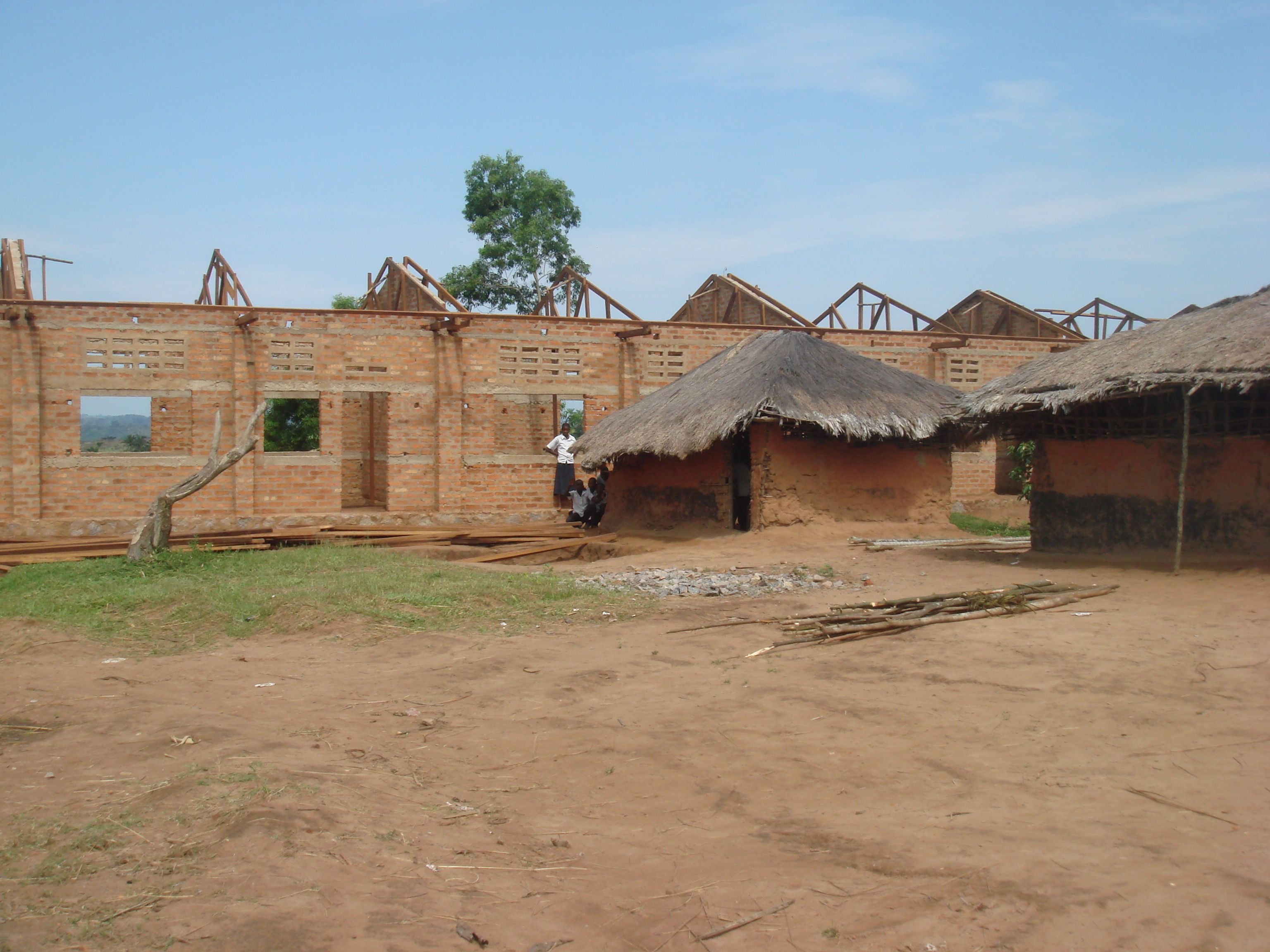 New brick school being built behind current mud hut classrooms
