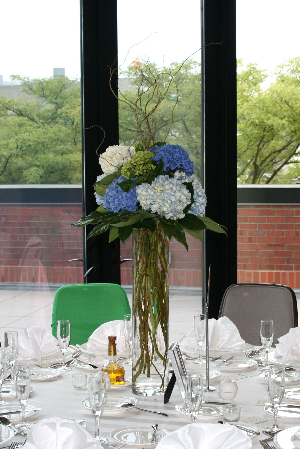 white, green, and blue hydrangea, curly willow tall centerpiece. Glass vase  filled