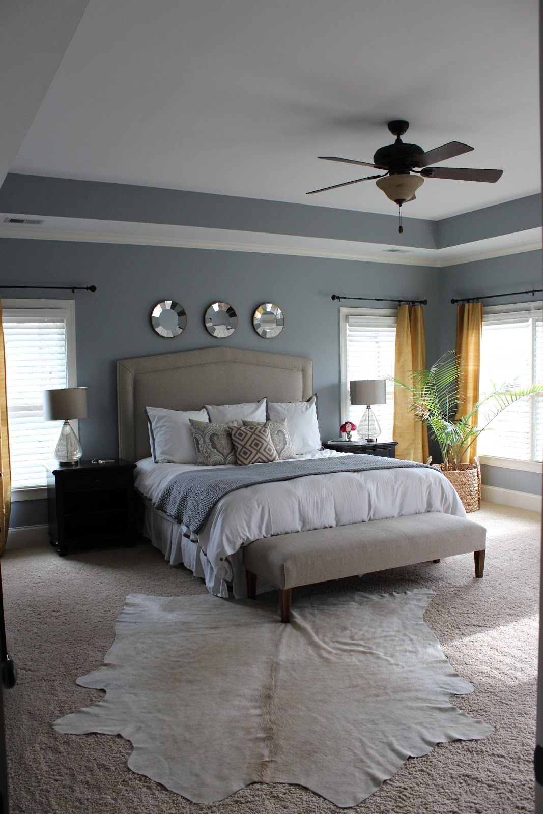 grey and white master bedroom with pop of gold in curtains