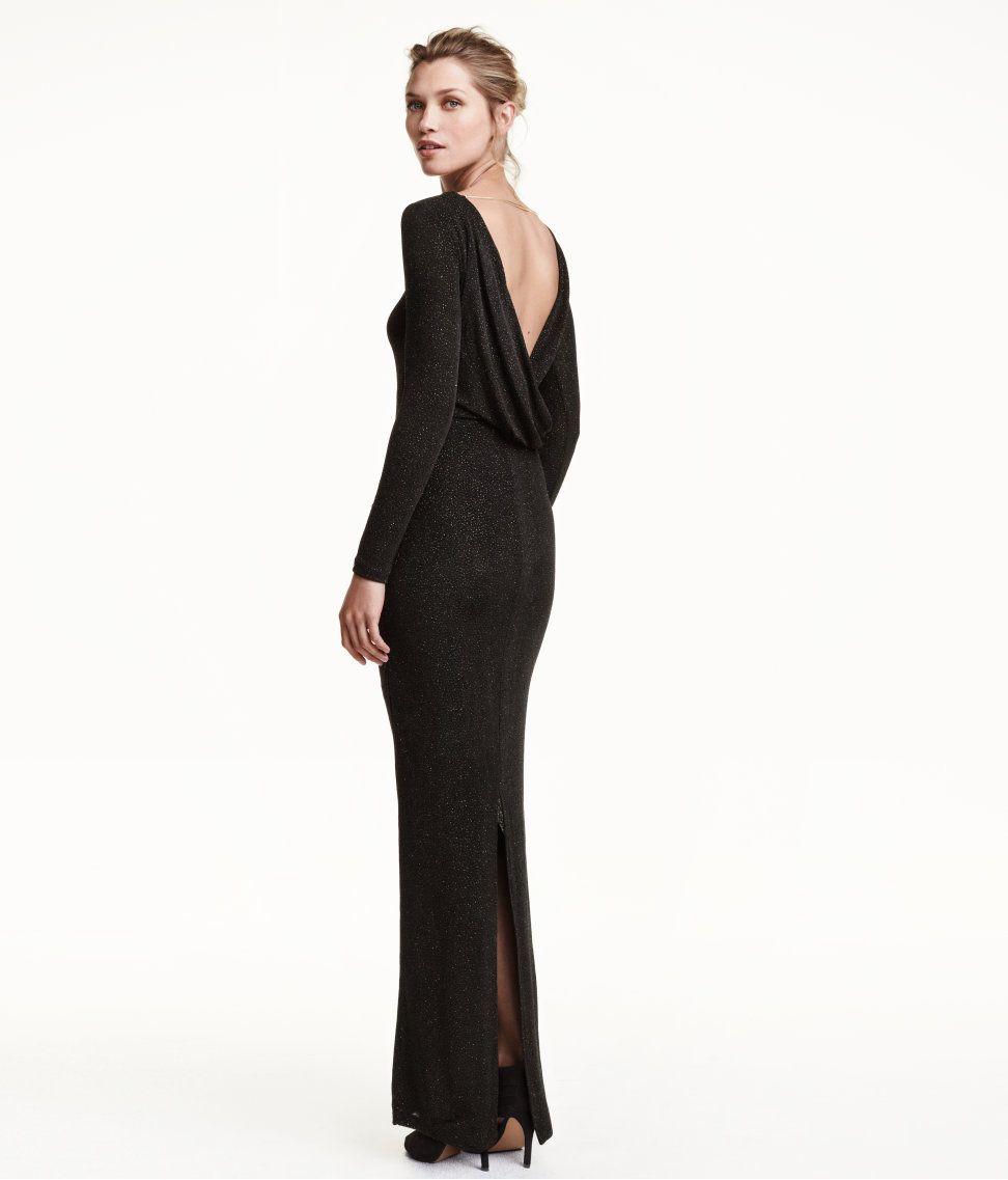 928cd864a9c7 En lång, figurnära klänning i glittrig trikå. Klänningen har djupt ringad,  draperad rygg och ormlänk i metall i nacken. Lång ärm. Slits bak.  Trikåfodrad.