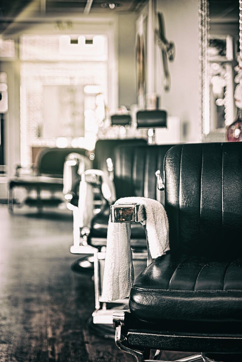 Shallow Focus Photography Of Black Leather Styling Chairs With White Towels