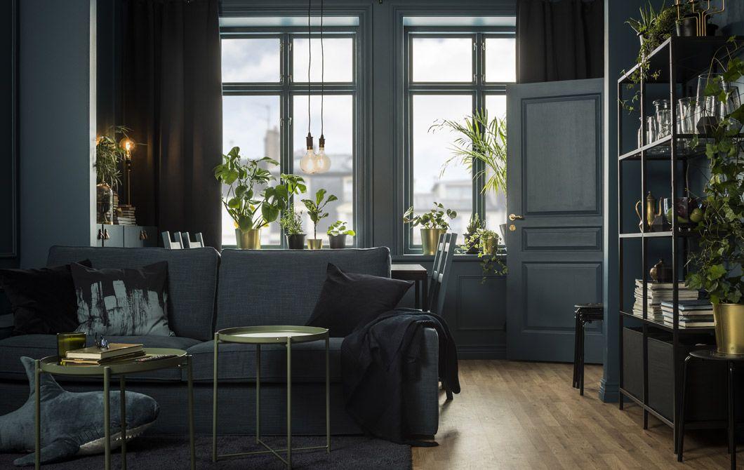 Un soggiorno in tonalità blu scuro, oro e nero arredato con divano e ...