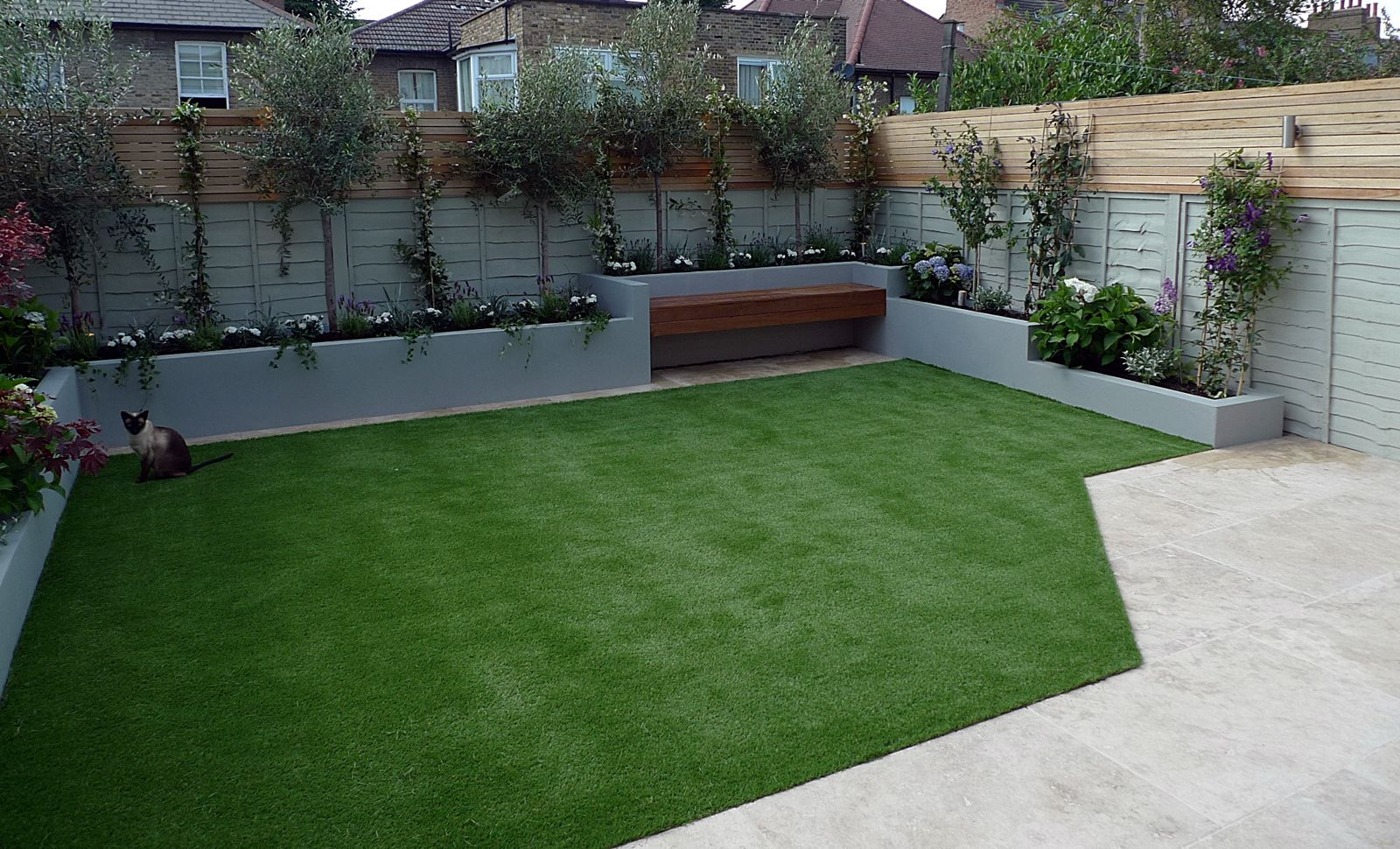 small-garden-design-raised-beds-artificial-grass-travertine-paving