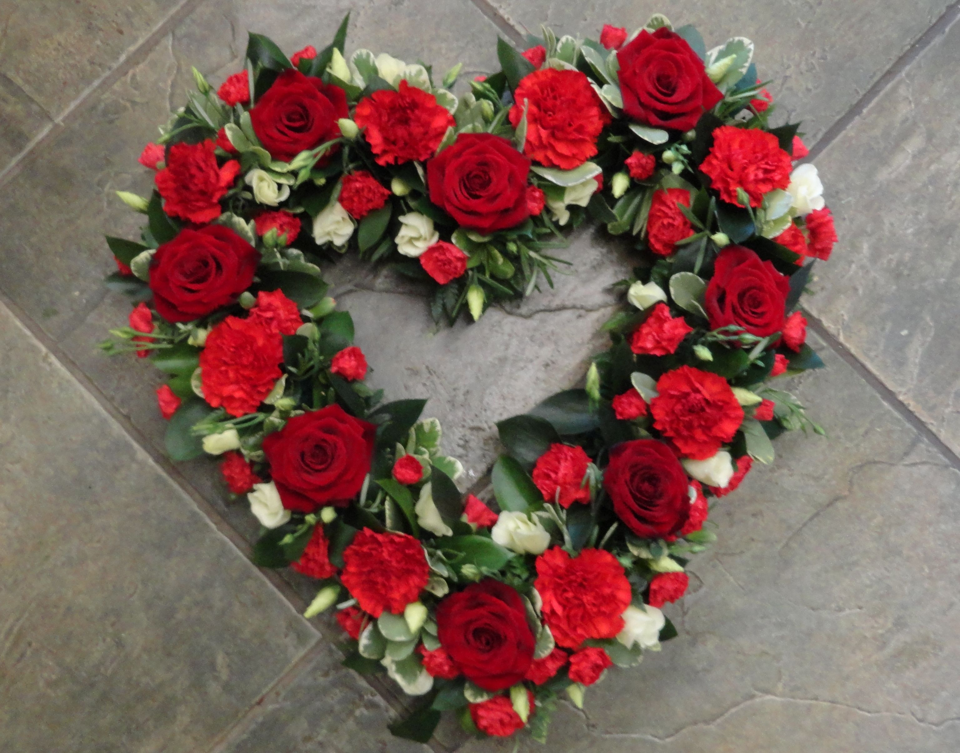 Loose style open heart of red flowers including roses and