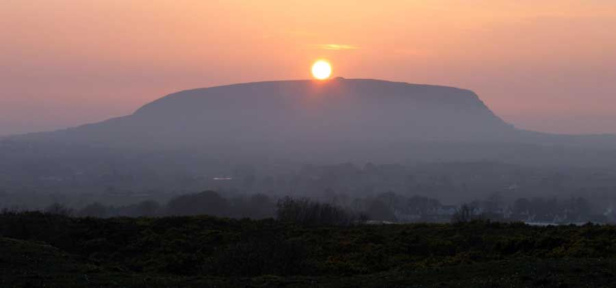 The sunset on the 28th of March 2012, viewed from Cairns Hill west in County Sligo. The sun is dropping over Queen Maeve's Cairn, a massive neolithic monument on the summit of Knocknarea, thought to date to around 3,200 BC. The photo is taken from one of the two massive stone cairns on Cairns Hill, contemporary with Queen Maeve's Cairn.    http://www.carrowkeel.com/