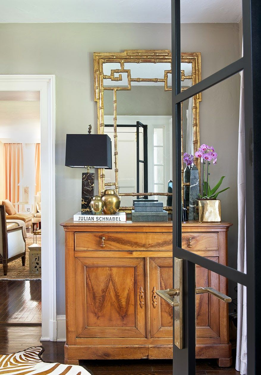Stunning Entrance-black, glass & brass door, black marble lamp & obelisk, gold chinoiserie mirror, brass jars, lacquered gold floral vase and square upon square upon square. In Good Taste: Laura Tutun Interiors